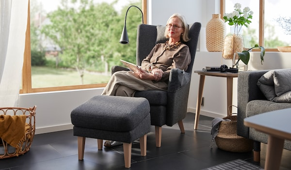 Britt Monti seated in an OMTÄNKSAM armchair in the bright corner of a room with large windows. A garden in the background.