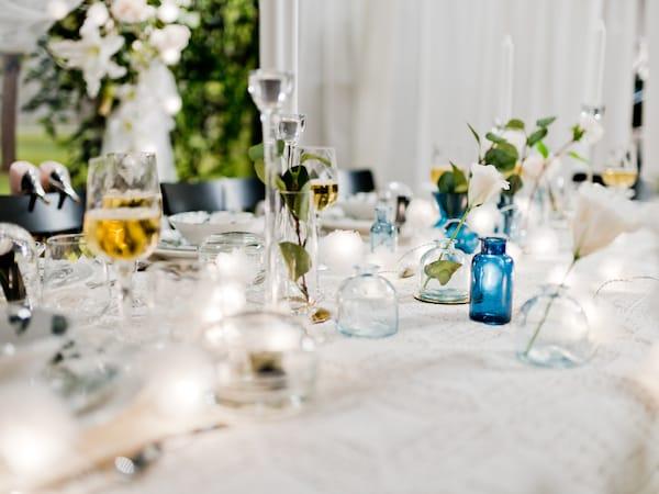 Bröllopsdukning i krispigt vitt med ljusslinga och små blå vaser i olika storlekar som dekoration.