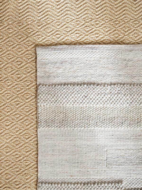 BRÖNDEN tæppe ligger symmetrisk oven på et VISTOFT tæppe. Begge er i lyse, naturlige farver med diskrete mønstre.
