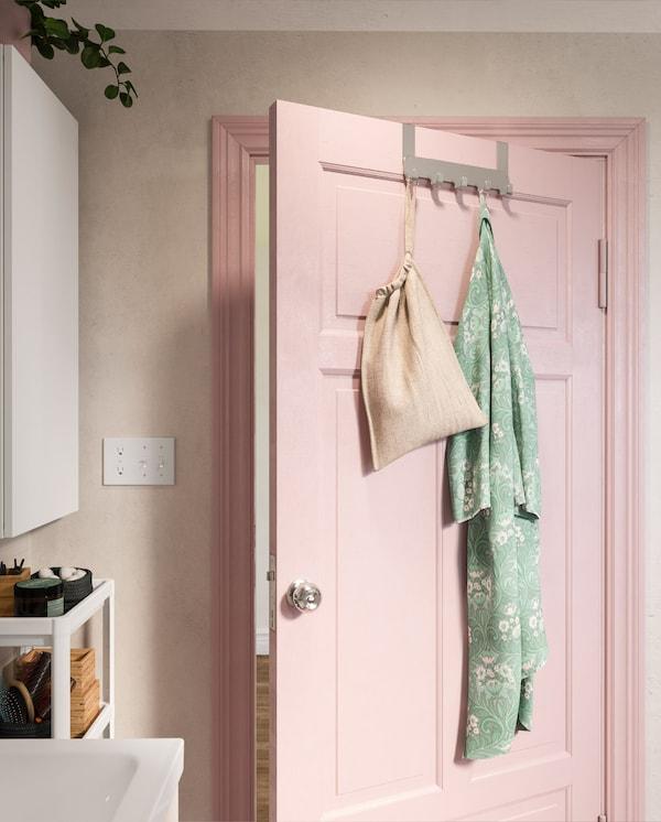 BROGRUND hanger for door in stainless steel hangs on a pink bathroom door. A turquoise bathrobe hangs on one of the hooks.