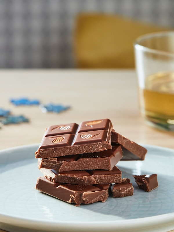 Broken pieces of chocolate are piled up on a blue plate. In the foreground, a half-filled cup of beverage and blue puzzle pieces are seen.