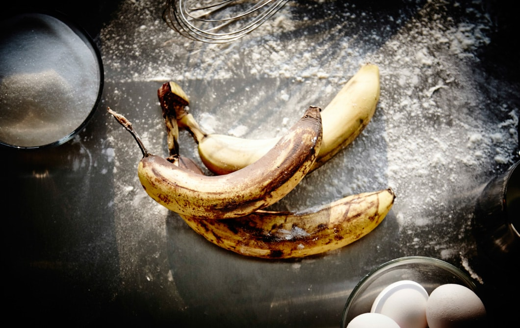 Brown bananas, next to cooking ingredients like eggs, sugar and flour