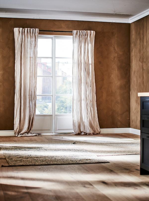 Brunt rum med franske døre med gardiner af krøllet hør og lysebrune tæpper af naturmaterialer på trægulvet.