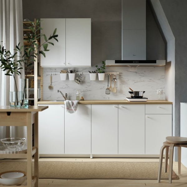 ベースキャビネットとウォールキャビネットで構成されたホワイトのKNOXHULT/クノックスフルト キッチン。その正面には冷蔵庫があり、奥にはダイニングエリア。