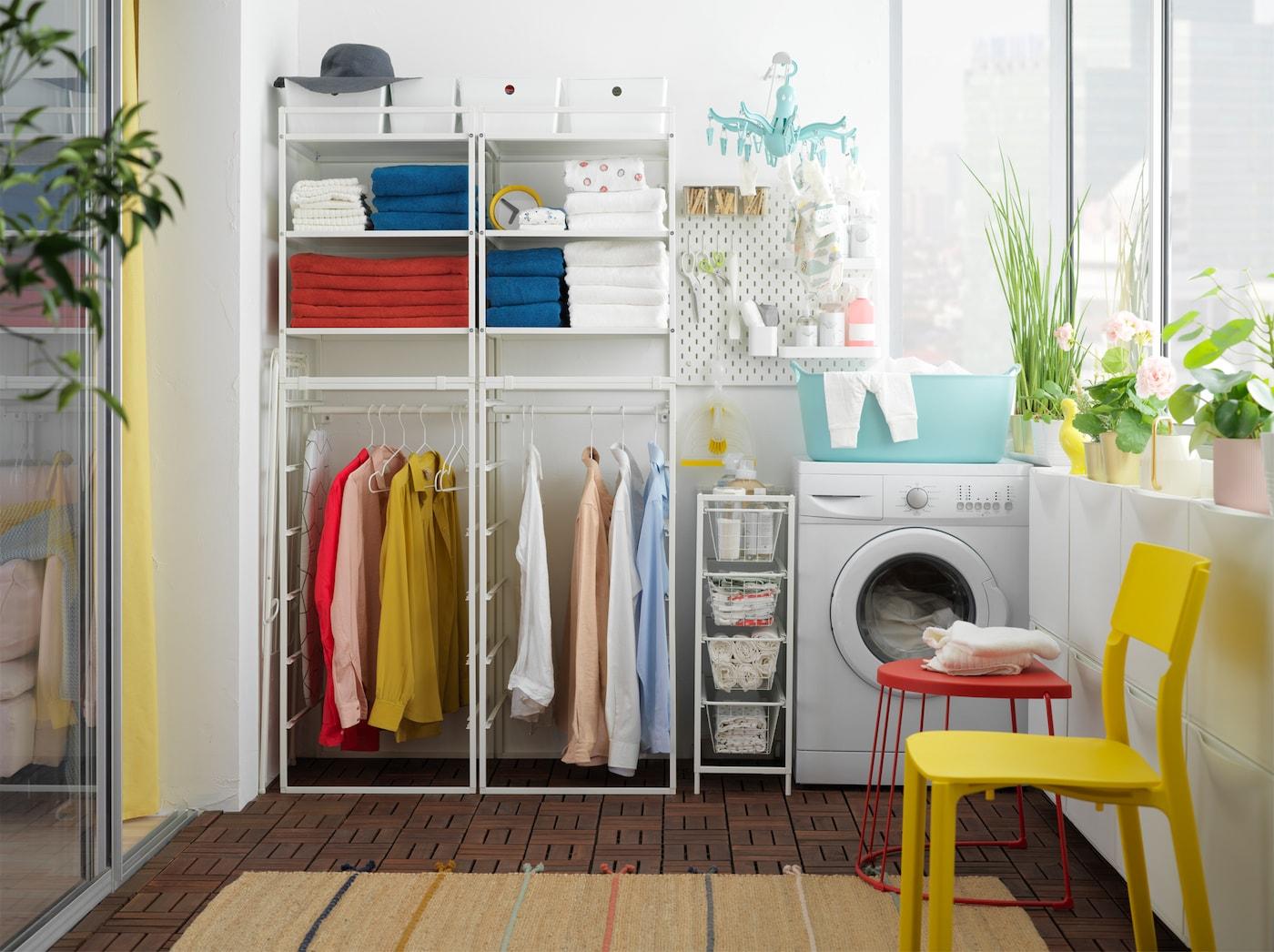Buanderie équipée d'une étagère JONAXEL. Des serviettes sont rangées sur ses tablettes et des vêtements accrochés à ses tringles, à proximité d'un lave-linge.
