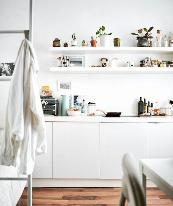 Bucătărie complet albă, cu etajere fără uși și o scară de pat în fundal.