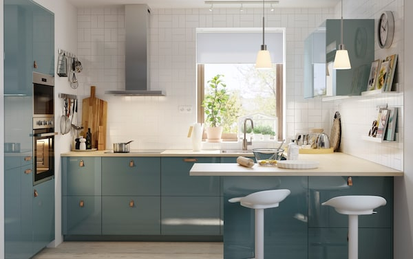 Bucătărie cu faianță albă cu uși KALLARP, turcoaz, cu luciu intens și o insulă de bucătărie cu două scaune înalte.
