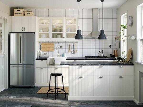 Bucătărie tradițională alb închis, cu o combinație de uși din sticlă SEKTION/HITTARP, cu lumina pătrunzând prin fereastră.
