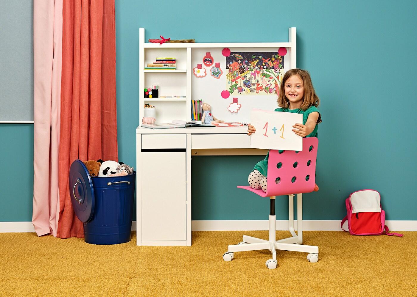 Budoucí prvňáček u bílého psacího stolu MICKE sedí na růžové židli JULES