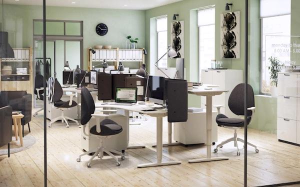 Büro mit BEKANT Ecktischen zum Sitzen & Stehen, HATTEFJÄLL Drehstühlen & einer Abschirmung für Schreibtisch