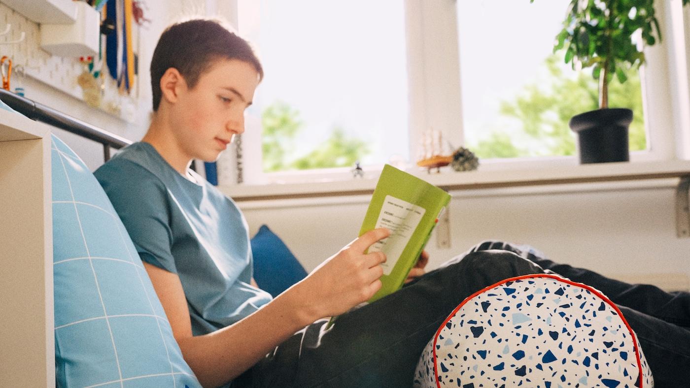 Büromöbel für Kinder: Ein Schulkind sitzt auf dem Bett und liest.