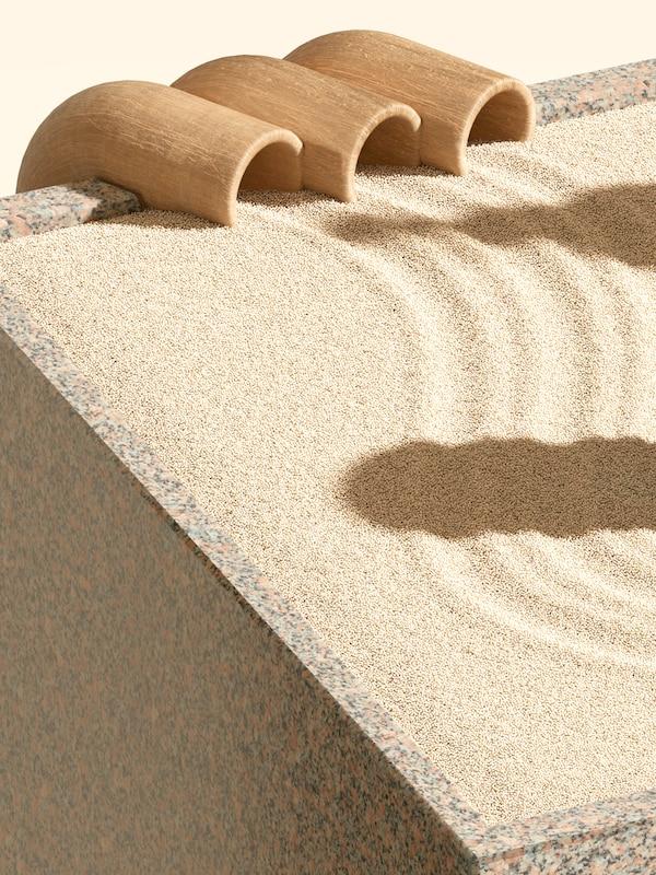 Buktende spor fra tre rør av tre på kanten av ei kasse av granitt full av gul sand.
