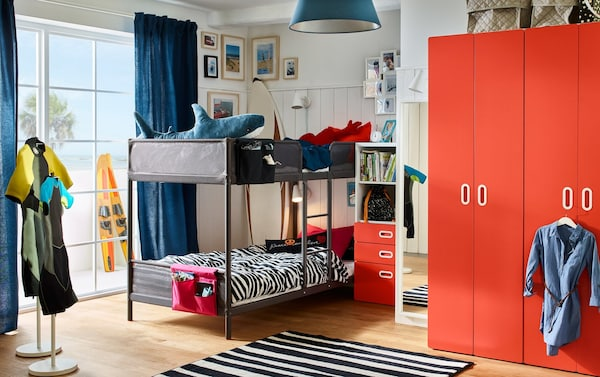 Bunkbeds sit in this bright, colourful children's room that has a STUVA/FRITIDS wardrobe and bookcase in white/red.