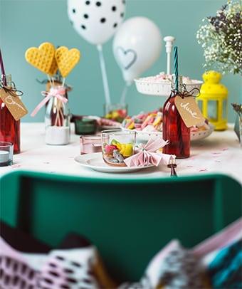 Bunt gedeckter Tisch mit Schleifen, Luftballons, Süßigkeiten & DIY Elementen