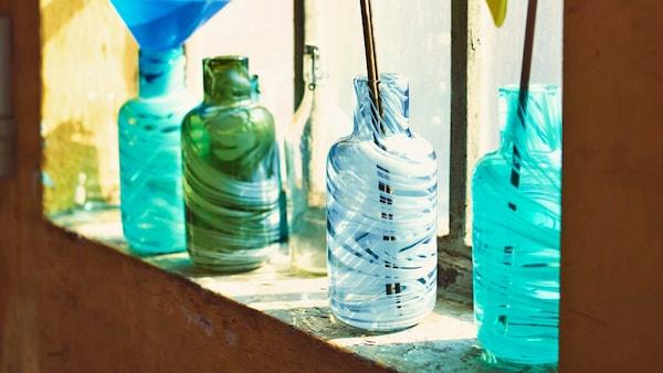Bunte Vasen auf einem Fensterbrett, gefertigt aus recyceltem Glas