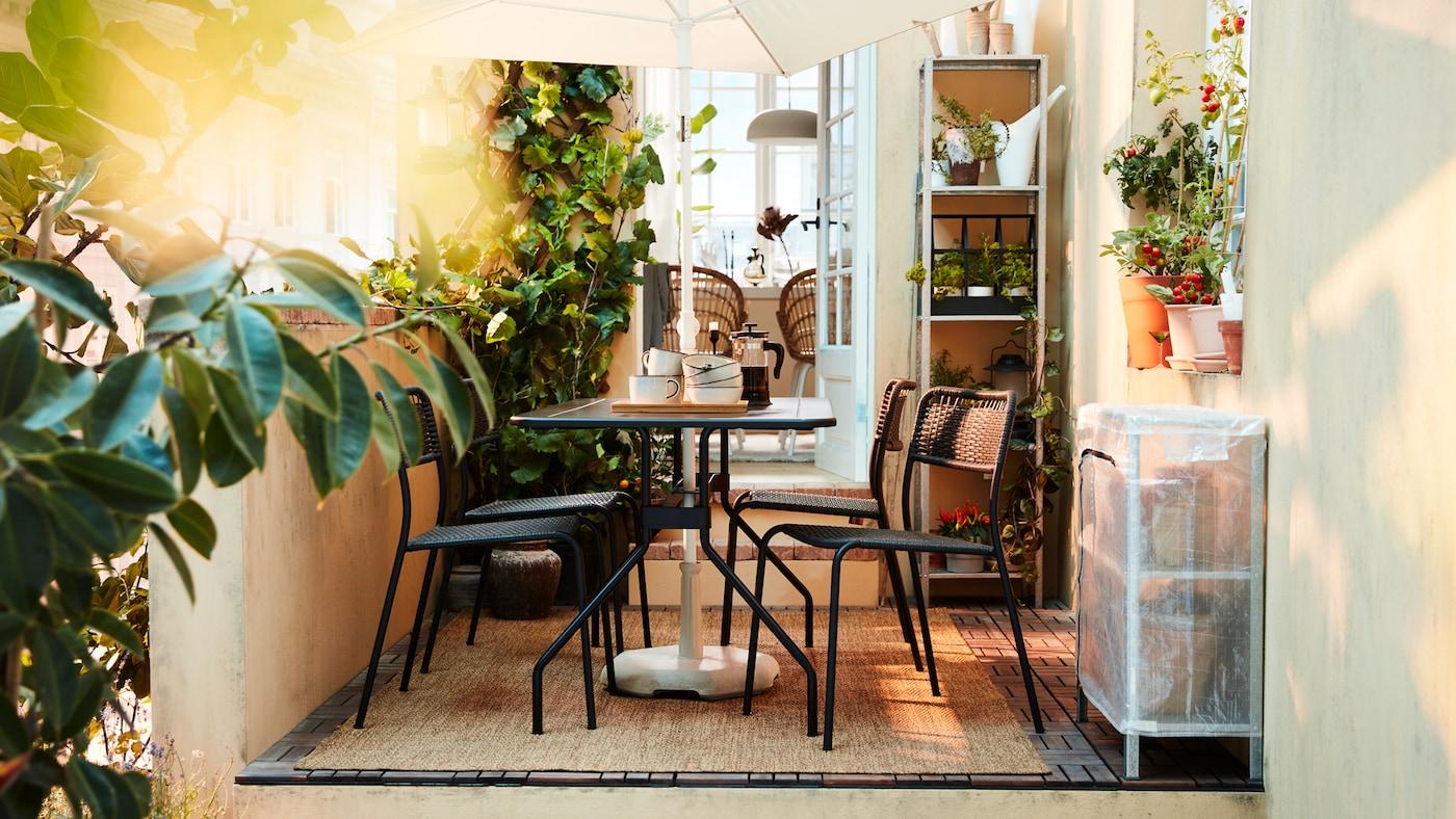 ブラックのダイニング家具セット、ホワイトのパラソル、たくさんの植物、平織りラグがある緑豊かな屋外スペース。