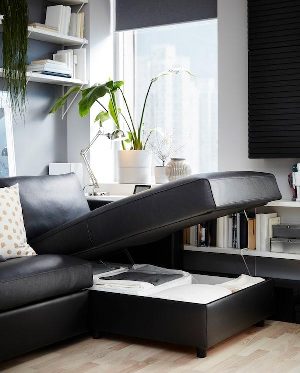 ブラックの寝椅子付き革製ソファベッド。寝椅子が開いた状態で、中には布団が収納されています。ホワイトのシェルフとグリーンプラント。