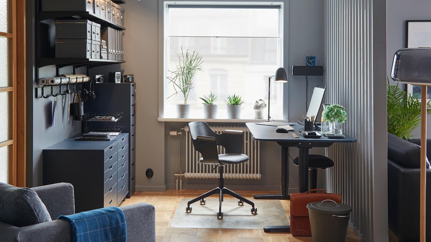 Bureau assis/debout BEKANT, linoléum bleu/noir, dans un espace de travail aux couleurs coordonnées, avec une chaise de conférence et des rangements.
