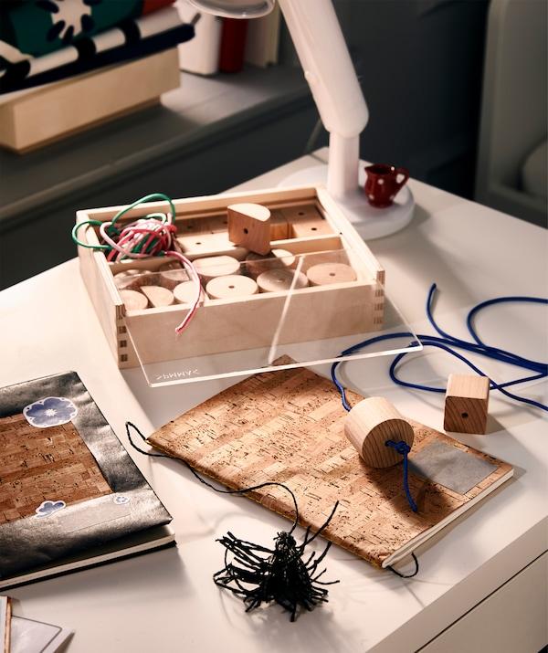 Bureau avec travail en cours: couvertures de cahier personnalisées avec autocollants, et signets confectionnés avec des perles à enfiler.