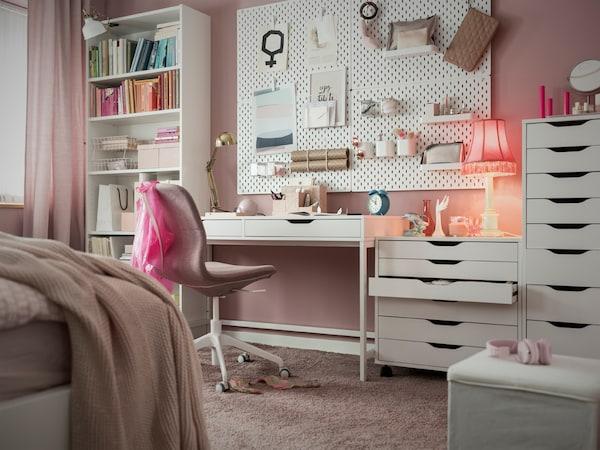 Bureau et caissons à tiroirs ALEX, et chaise rose placés dans une chambre peinte en rose.