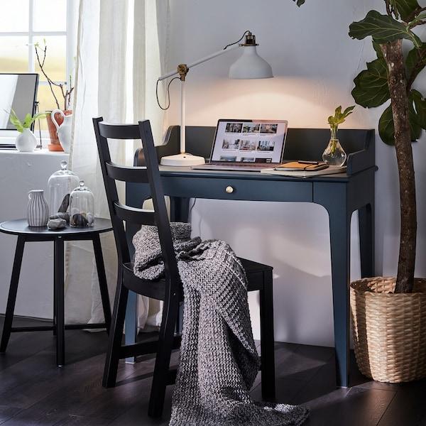 Bureau LOMMARP bleu-vert foncé. Dessus, un portable et une lampe de table allumée. Devant, une chaise noire sur laquelle on a déposé un jeté gris.