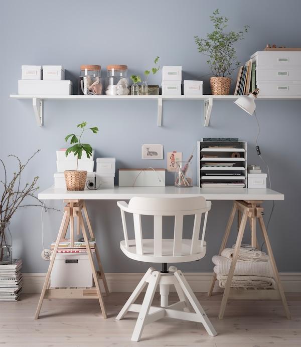 Bureau sans tiroir blanc et piètement en bois clair. L'ordre règne grâce à la présence d'une étagère murale, de nombreuses boîtes ainsi que de plusieurs pots et vases.