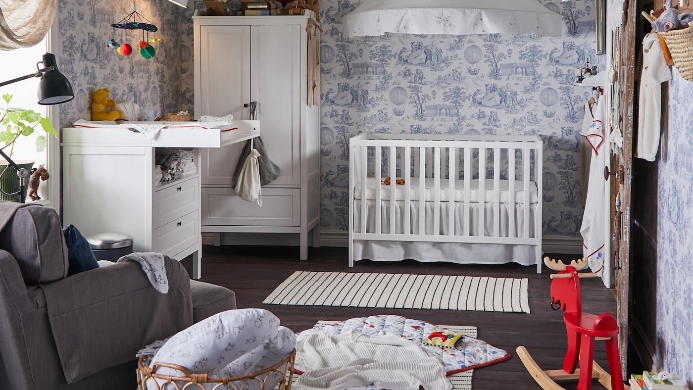 ブルーとホワイトの壁紙を使用したトラディショナルスタイルの子ども部屋。SUNDVIK/スンドヴィークのベビーベッド、ワードローブ、おむつ替え台が配置されている。