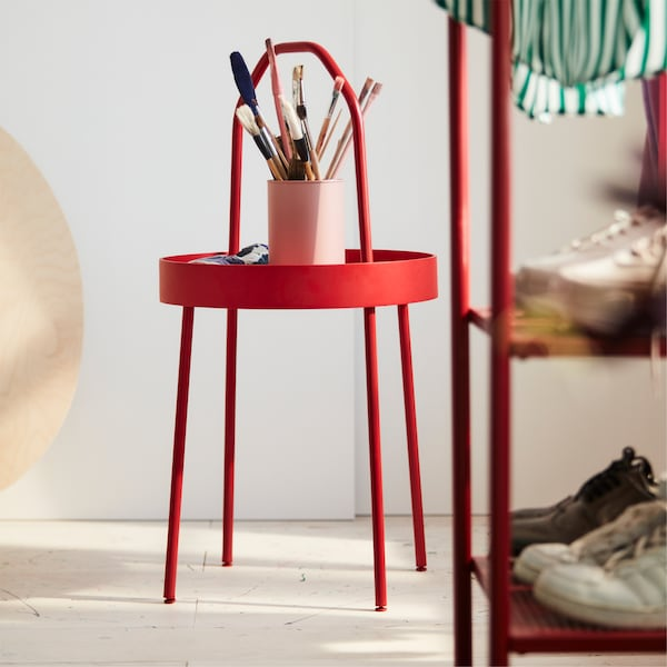 BURVIK side table in red where painting brushes are stored. BURVIK is standing next to a white wall in a bedroom.