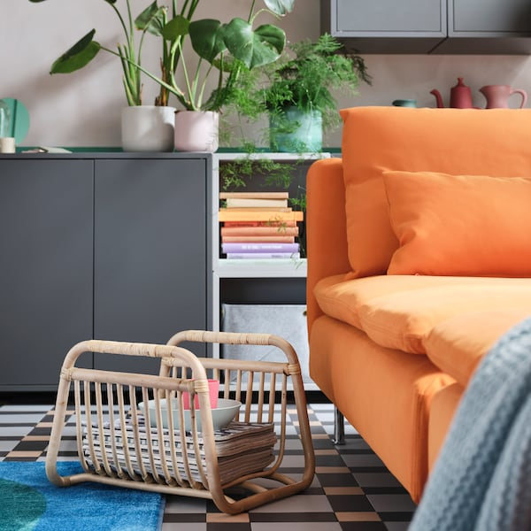 BUSKBO magazine stand in light rattan stores magazines, a bowl and a mug, and it stands on the floor next to an orange sofa.
