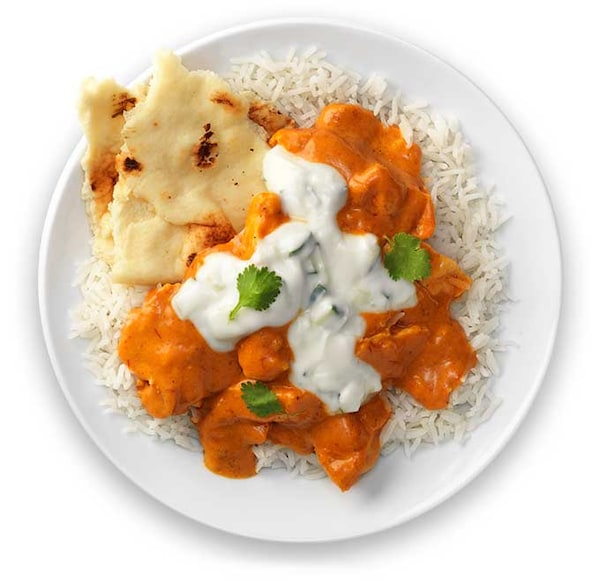 Butter chicken on a white plate.