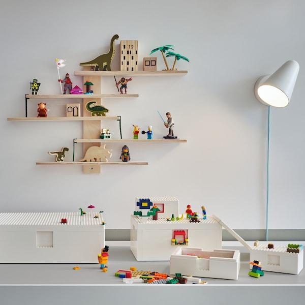 BYGGLEK LEGO®-Steine und -Schachteln liegen auf einem weißen Spieltisch. Eine weiße Wandleuchte und ein Regal mit Spielsachen darauf hängen an der Wand.