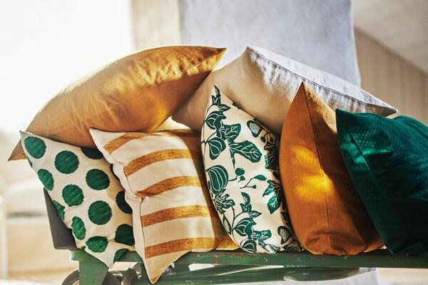 Gelb und grün gemusterte Kissen auf einem grünen Gestell.