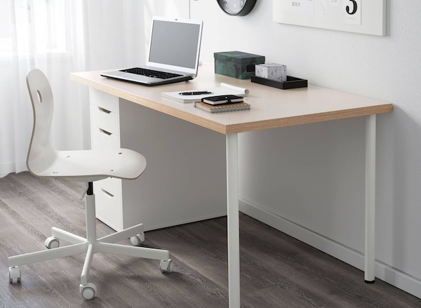 A dining chair next to an office desk with drawers, and a laptop and stationery on top.