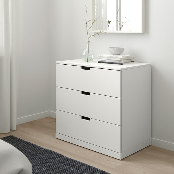 A light, Scandinavian style bedroom with a white IKEA NORDLI chest of drawers with some books and a vase on top.