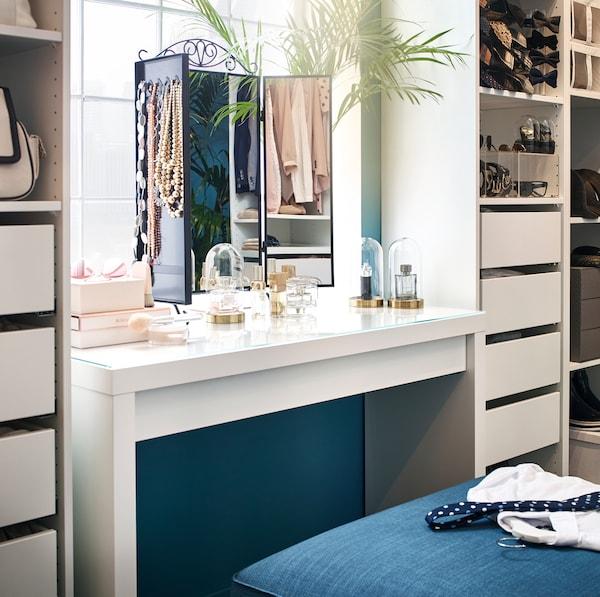 Bijeli IKEA MALM toaletni stolić s KARMSUND ogledalom za stol od crne žice i SAMMANHANG malim staklenim vazama.