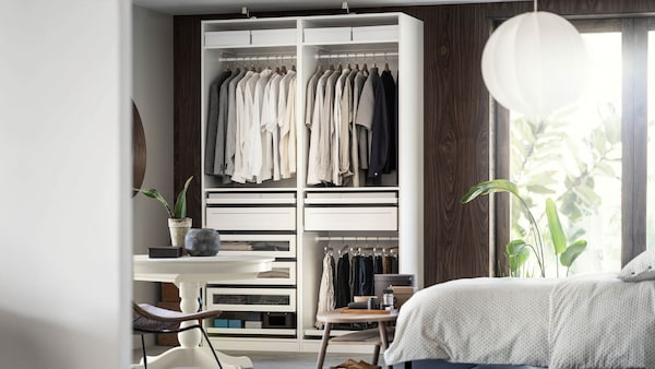 Wardrobe filled with clothes in an organized bedroom.