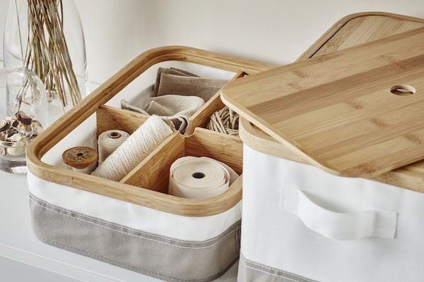 Kasten aus Stoff in weiß und grau mit Deckel aus Bambus mit mehreren Garnrollen in Fächern.