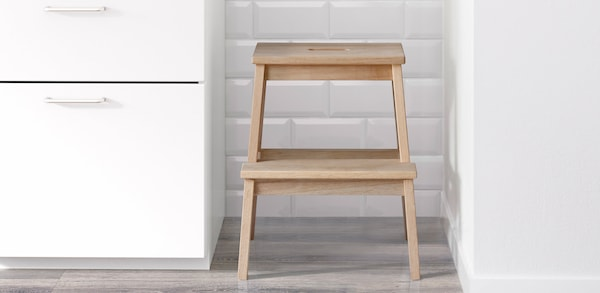 Wooden step stool stored in between white cabinets and a white wall