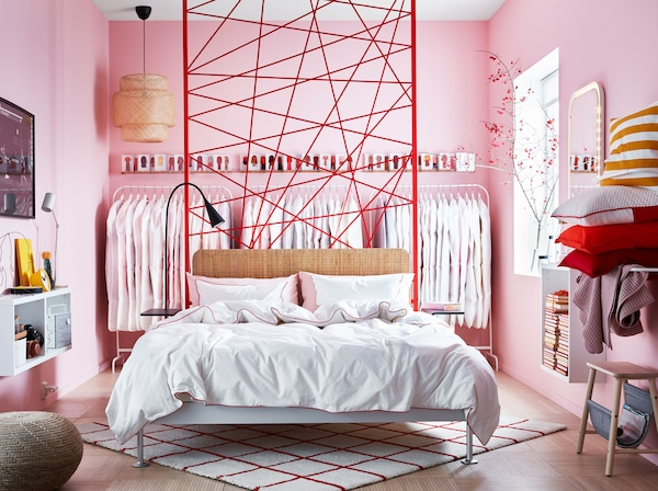 A pink wall-to-wall bedroom with a sofa bed in the middle of the room and crisp white bedsheets with red piping.