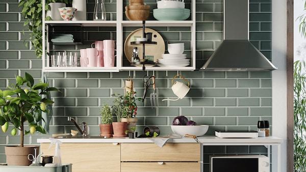 Vihreäksi laatoitettu keittiö, avohyllyillä asitoita, liesituuletin, yrttejä pöydällä ja pieni sitruunapuu.