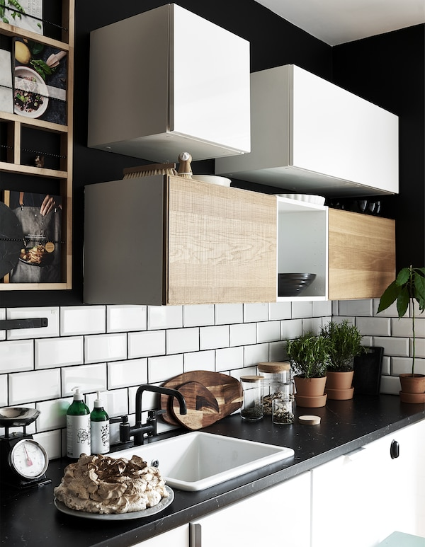 Cabinets hung on a wall above a worktop in a black-and-white kitchen.