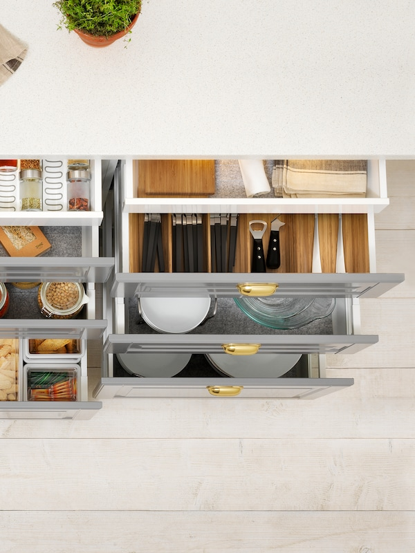 Cabinets with grey drawer fronts where all the drawers are open, containing dry goods, cutlery, cookware and tableware.