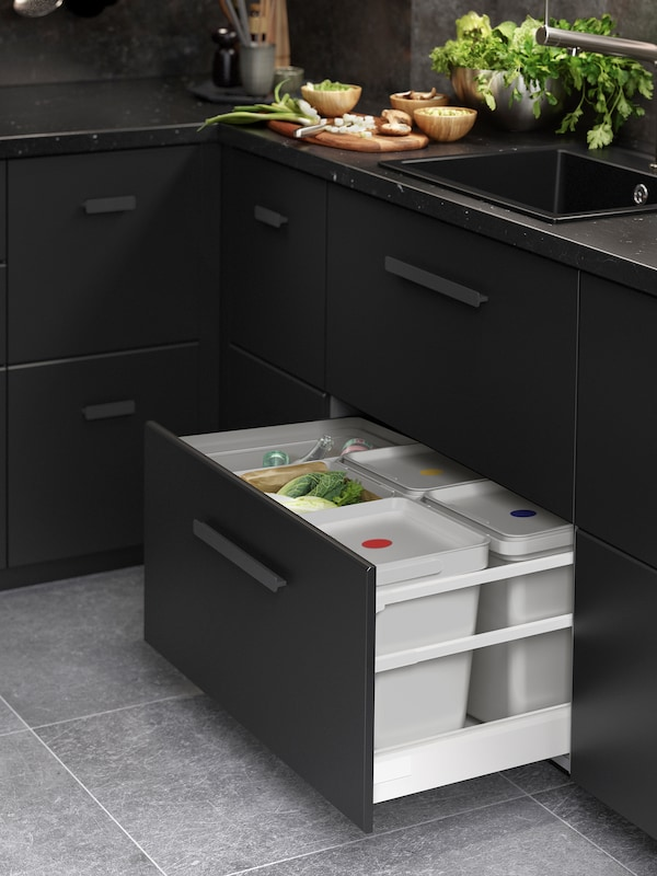 Cabinets with KUNGSBACKA anthracite drawer fronts. One drawer is open and has light-grey HÅLLBAR bins inside.