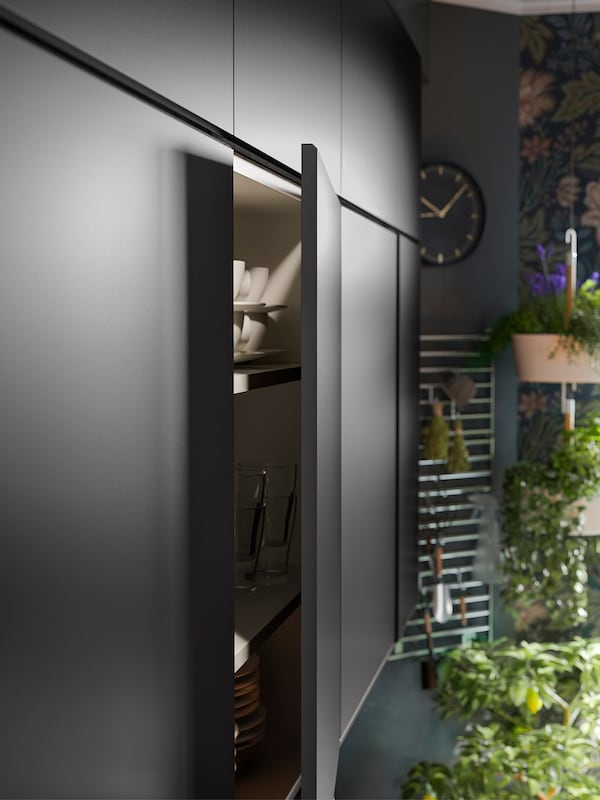 Cabinets with KUNGSBACKA anthracite kitchen cabinet door fronts. One door is open showing tableware stored inside.