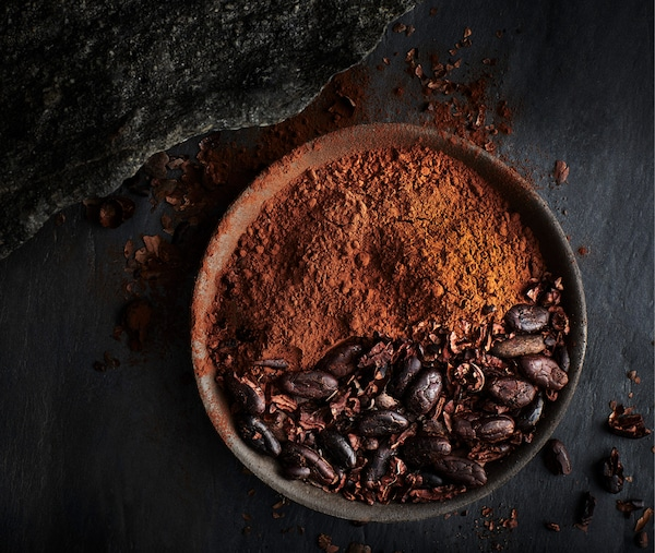 Cabosses et fèves de cacao sur une assiette noire, avec feuilles vertes, vues d'en haut.