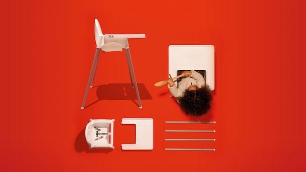 Cadeira alta com tabuleiro em branco e criança a brincar com uma colher. Ao lado, parte de outra cadeira num fundo vermelho.