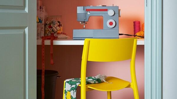 Cadeira amarela JANINGE diante dun escritorio cunha máquina de coser enriba.