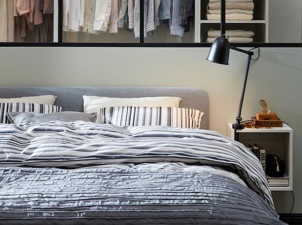 Cadru de pat cu tapițerie gri, lenjerie de pat în dungi și o noptieră albă cu lampă neagră.