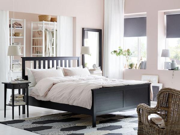Cadrul pentru pat HEMNES, negru maroniu, de la IKEA , este realizat din lemn masiv și are stinghii la tăblie.  Este finisat pe toate laturile, astfel că poți îndrăzni să așezi patul în mijlocul dormitorului.