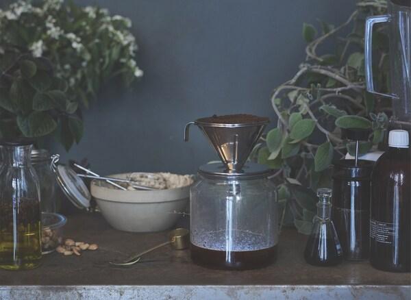 Café en train de s'écouler dans une carafe en verre, posée sur une table avec d'autres bocaux et ingrédients.